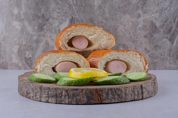 Нарезанный колбасный хлеб, огурцы и лимон на доске на мраморном столе.
