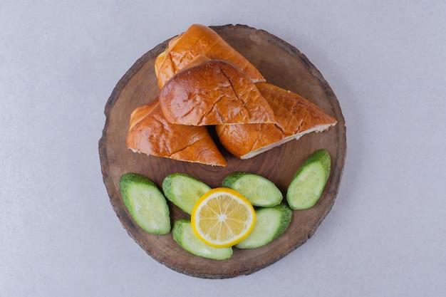 Нарезанный колбасный хлеб, огурцы и лимон на доске на темной поверхности