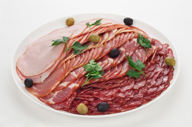 Sliced sausage, carbonate, balyk, meat. on a plate on a white