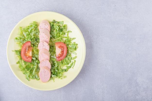 노란색 접시에 소시지와 토마토를 슬라이스.