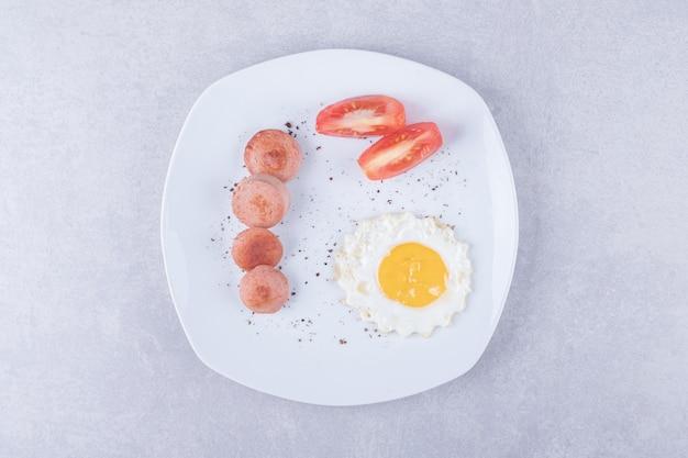Salsicce e uova affettate sul piatto bianco.