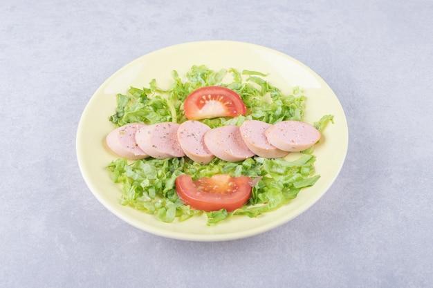 Salsicce e pomodori affettati sulla zolla gialla.