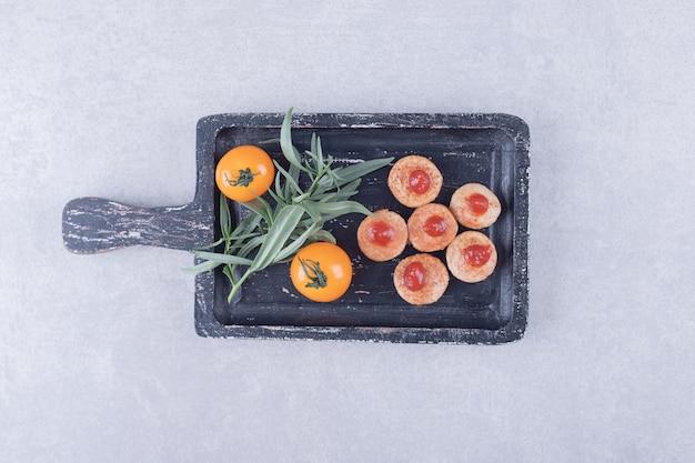 블랙 보드에 케첩과 토마토와 소시지를 슬라이스.