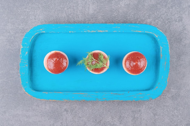 Salsicce affettate con ketchup sul bordo di legno blu