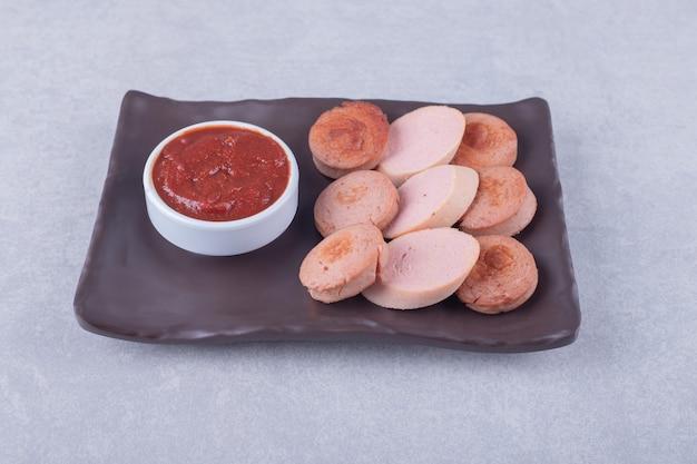 Нарезанные сосиски с кетчупом на темной тарелке.