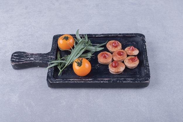 Salsicce affettate con ketchup e pomodori sul bordo nero.
