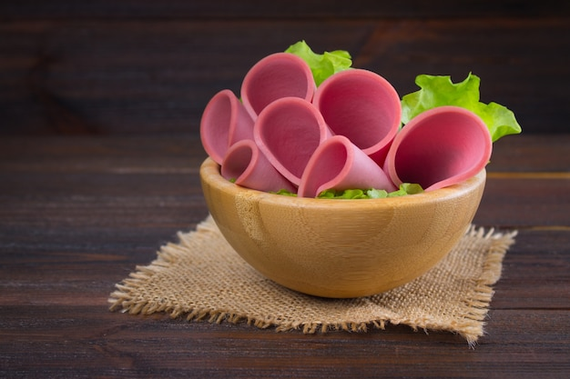 Sliced sausages with salad leaves on the wood background