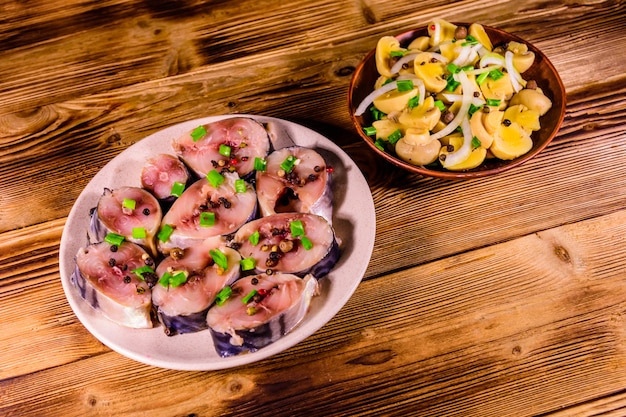 Sliced scomber fish and canned mushrooms with green onion on a ceramic plates on rustic wooden table