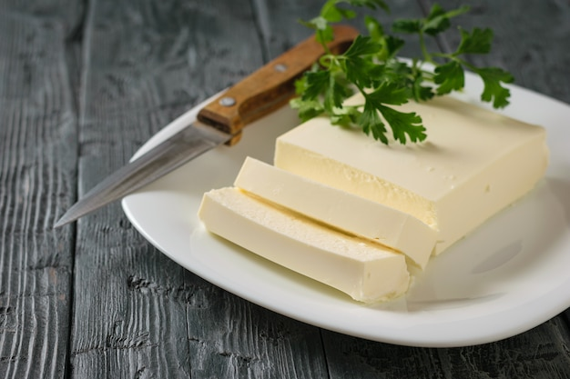 Sliced serbian cheese with a knife and parsley leaves on a black wooden table.