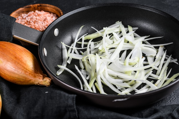 Sliced shallot in a pan, cooking fried onions. black background. top view