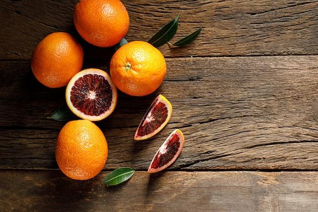 Sliced sicilian blood oranges fruits over old dark wooden. top view.