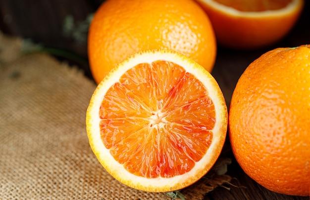 古い暗い木製の背景の上にスライスしたシチリアのブラッドオレンジの果実。