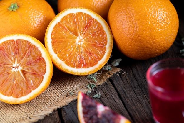 Нарезанные сицилийские кровавые апельсины фрукты над старым темным деревянным фоном.