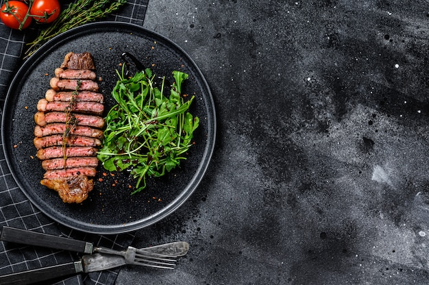 Sliced sirloin steak, marbled beef meat with arugula. black background. top view. copy space