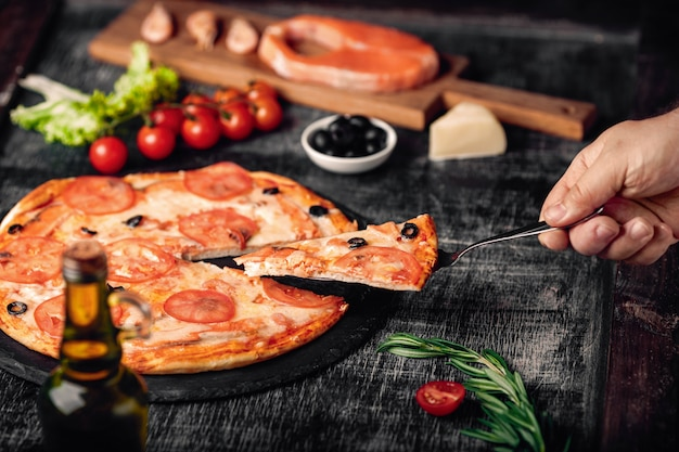 Sliced slice of pizza in hand with cheese, trout, tomatoes, olives and shrimps on chalk board.
