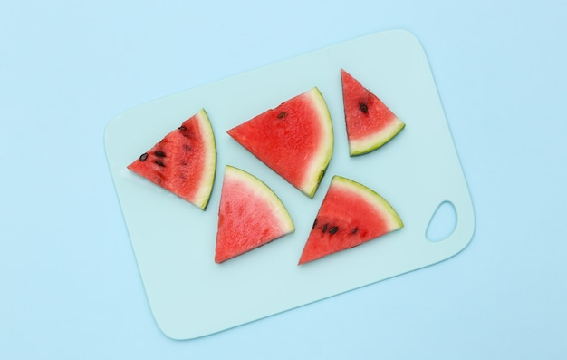 Sliced slices of ripe watermelon on a blue background. top view
