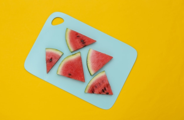 Sliced slices of ripe watermelon on a blue board. yellow background. top view