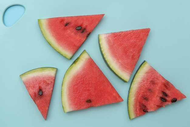 Sliced slices of ripe watermelon on a blue board