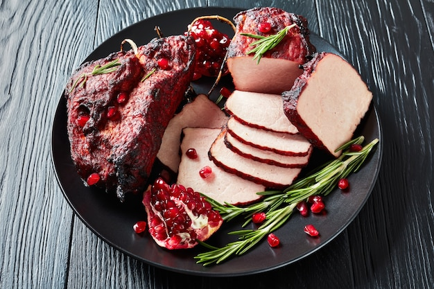 Sliced smoked barbecue pork tenderloin on a black platter with fresh garnet seeds and rosemary, on a black wooden table, view from above, close-up