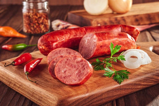 Ломтики копченой колбасы калабрезе на деревянном столе с ингредиентами - крупный план