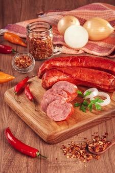 Нарезанная копченая колбаса калабрезе на деревянном столе с ингредиентами