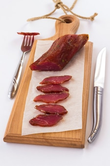 Sliced smoked meat on a cutting board. slice of meat on fork and knife