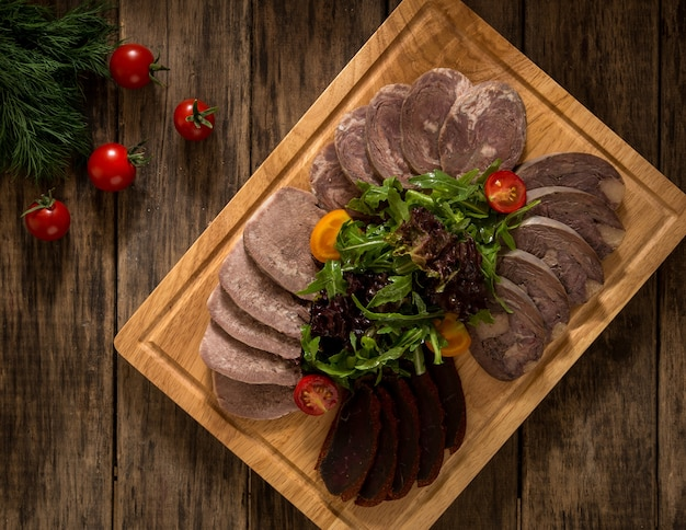 Нарезанное копченое мясо на разделочной доске, украшенной овощами, вид сверху