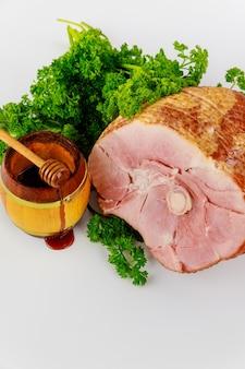 Sliced smoked pork ham with honey in wooden jar.