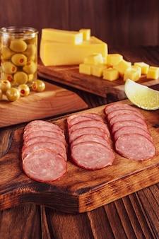 Нарезанная копченая салями на разделочной доске с детёнышами сыра и оливками
