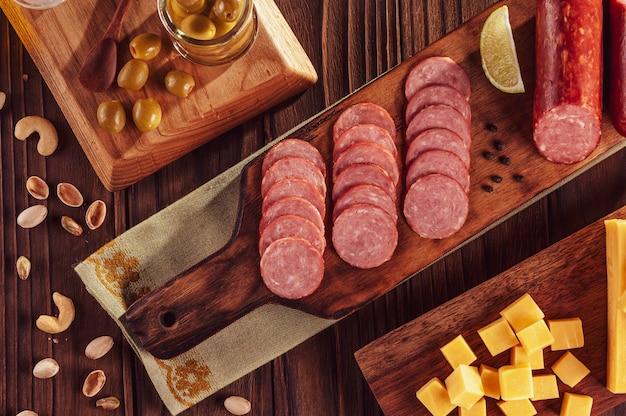 Нарезанная копченая салями на разделочной доске с детёнышами сыра, оливками, каштанами и фисташками