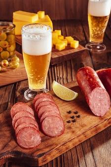 Нарезанная копченая салями на разделочной доске с двумя стаканами пива, кубиками сыра и оливками