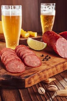 Нарезанная копченая салями с двумя стаканами пива, детёнышами сыра, оливками и фисташками