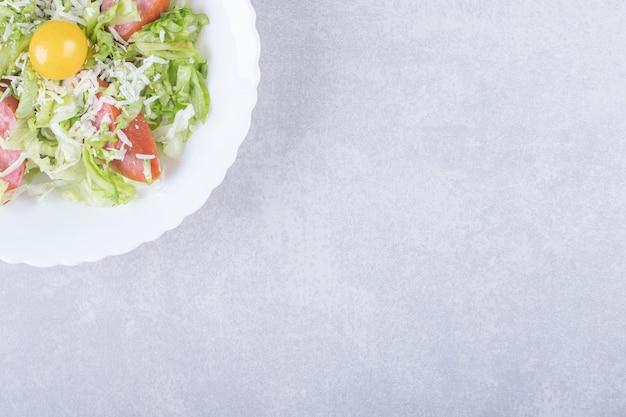 흰 그릇에 훈제 소시지, 양상추, 달걀 노른자를 슬라이스.