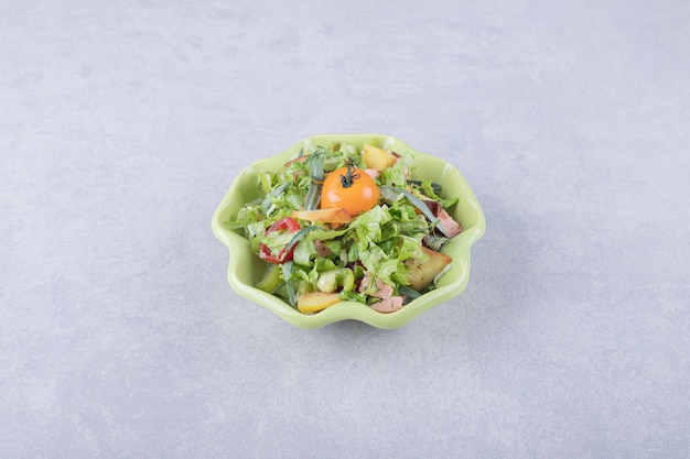 녹색 그릇에 훈제 소시지, 양상추, 토마토를 슬라이스.