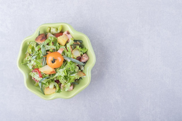 Sliced smoked sausages, lettuce and tomato in green bowl.