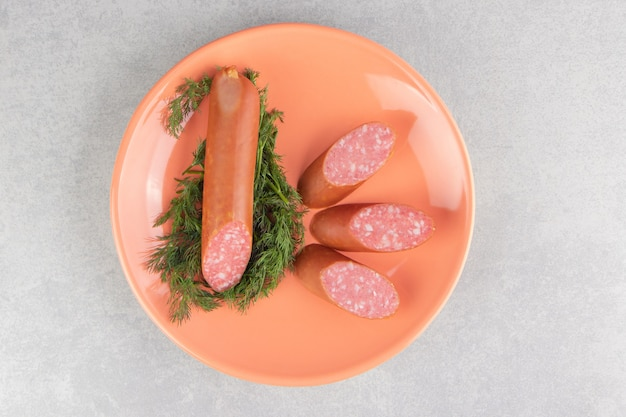 Sliced smoked sausages and parsley on orange plate.
