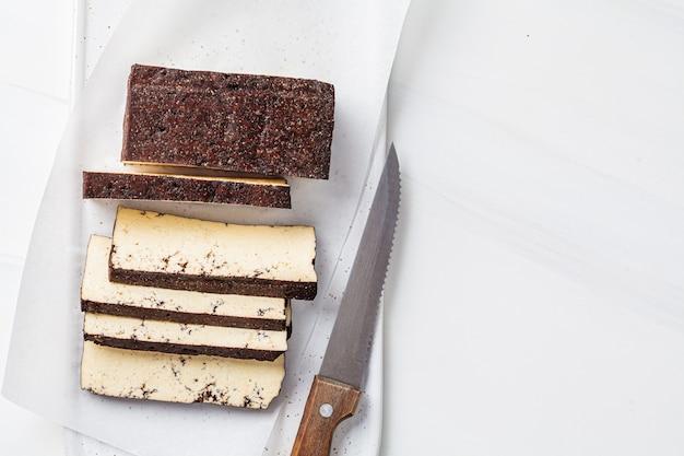 ホワイトボード、白い背景にスライスした燻製豆腐。ビーガンフードのコンセプト。