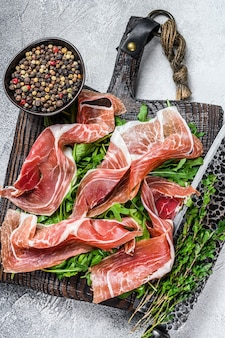 Sliced spanish jamon serrano ham or prosciutto crudo parma ham. white table. top view.