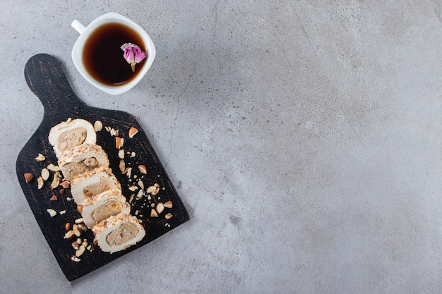 Sliced sponge cake roll with a cup of black tea placed on stone table .