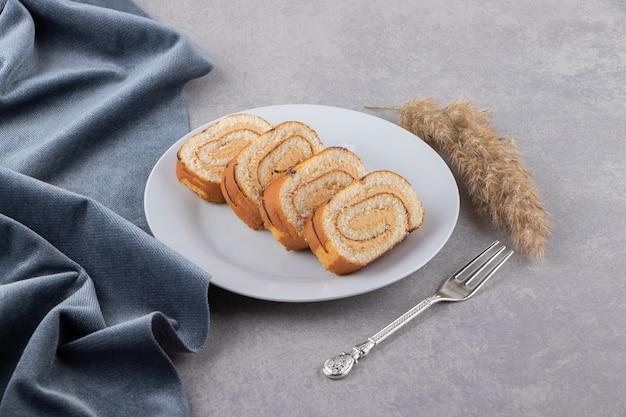 흰색 접시에 배치 스펀지 스위스 롤 케이크를 슬라이스.