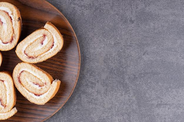 슬라이스 스폰지 스위스 롤 케이크는 나무 접시에 배치.