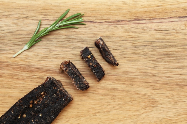 Sliced stick of biltong snack and rosemary seasoning on a wooden surface