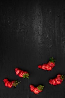 黒の背景に葉とイチゴをスライスしました。トップビュー、フレーム。コピースペース。夏のフルーツフードフレーム。