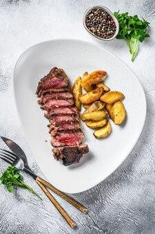 サーロインステーキとポテトのスライス。上面図。 Premium写真