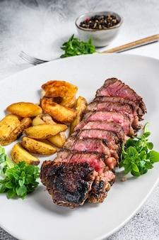 Sliced striploin steak with potato. white background. top view.