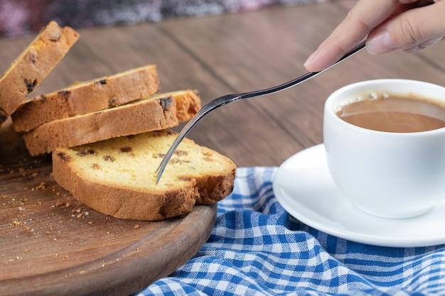Torta affettata dell'uva sultanina servita con una tazza di caffè.