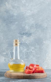 Fette di peperone rosso dolce con una bottiglia di vetro di olio su tavola di legno.