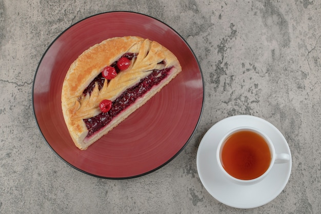 Sliced sweet cheesecake with tasty berries and a white cup of tea .