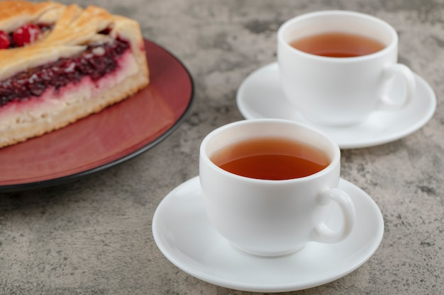 Sliced sweet cheesecake with tasty berries and white cups of tea .