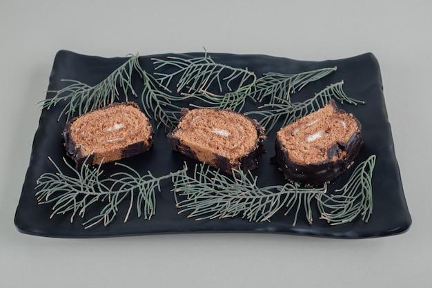 Rotolo di cioccolato dolce affettato su un piatto nero.